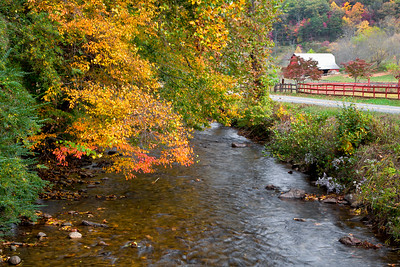 Autumn stream by the road with old, red barn in the background
